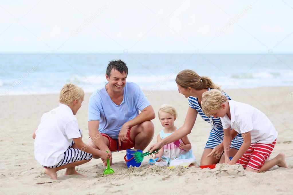 Happy family of five having fun on the beach