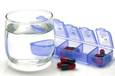 Oral medication red and black capsules in separated unit-dose box on white background.