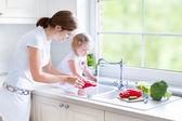 matka a její dcera mytí zeleniny