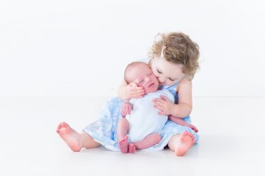 Toddler girl kissing her newborn baby brother