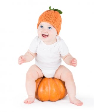 Baby girl playing with a huge pumpkin wearing a knitted pumpkin hat