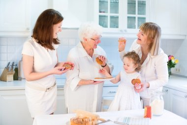 Four generations of women having fun together baking an apple pie