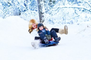Young happy mother and her adorable son having fun together on a sleigh ride in a snowy forest stock vector