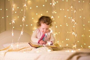 Little toddler girl reading a book
