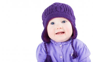 Baby girl wearing a purple sweater and knitted hat
