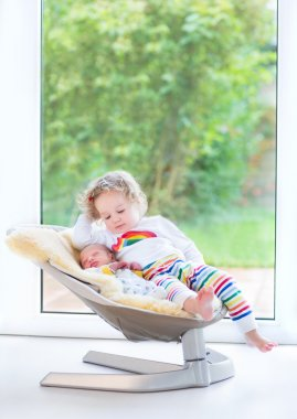 Newborn baby boy and his toddler sister relaxing