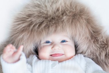 Baby girl with big blue eyes wearing a huge winter hat