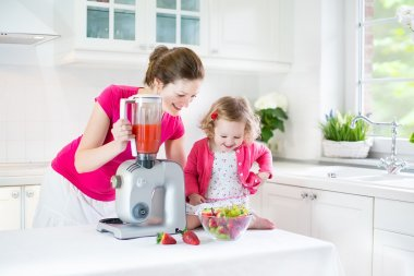 Irl and her young mother making fresh strawberry juice