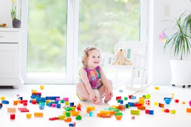 Toddler girl playing with colorful blocks