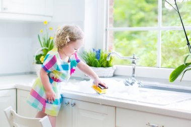 Girl washing dishes, cleaning with a sponge and playing with foam