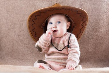 Baby wearing a cow girl outfit with a big hat