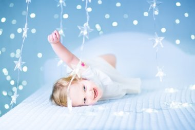 Toddler girl playing in a white bed