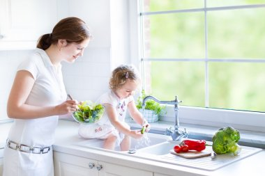 Mother and her daughter cooking salad together