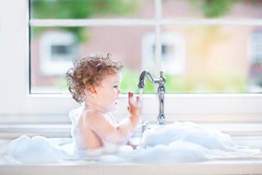 Baby girl with big blue eyes playing in a bath