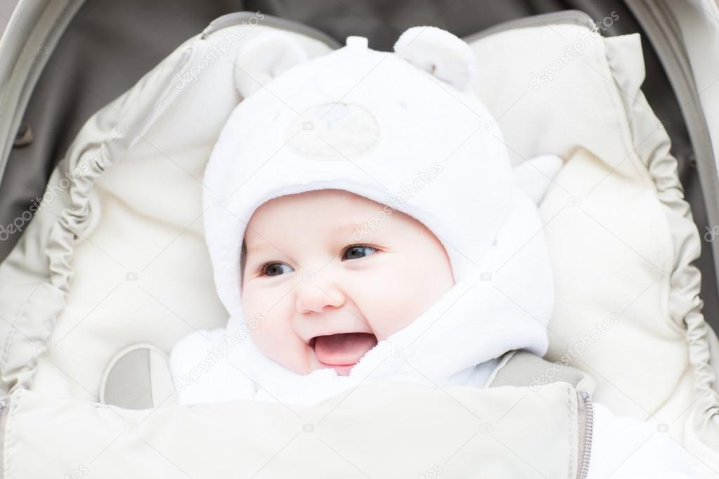 a5ff1d47049 Funny laughing baby in a teddy bear hat sitting in a stroller on c old  winter day — Photo by ...