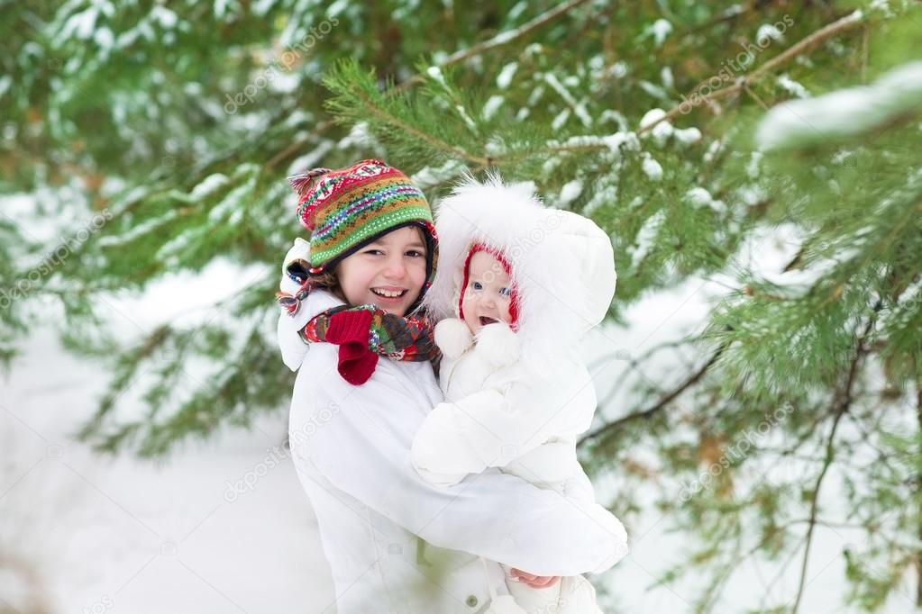 b51bba61d Boy hugging his baby sister in winter park — Stock Photo ...