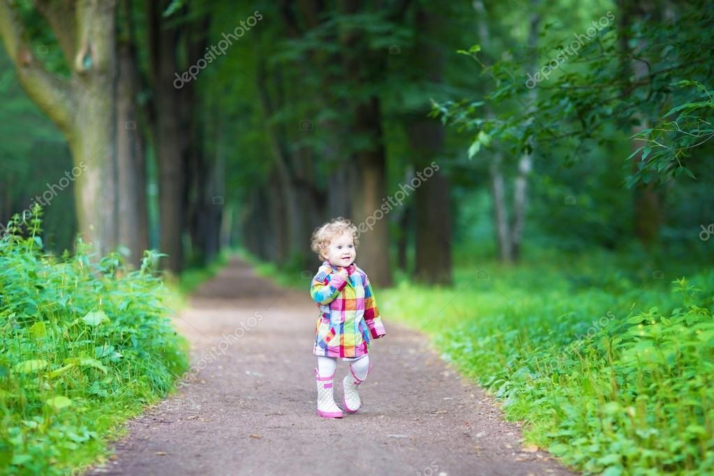 Baby girl in rain boots walking in a park