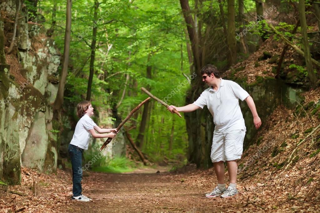 Father and son playing with sticks on a hike