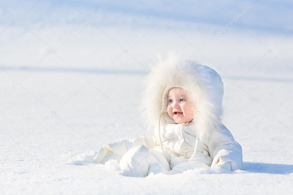 Baby girl in a warm white snow suit playing in snow