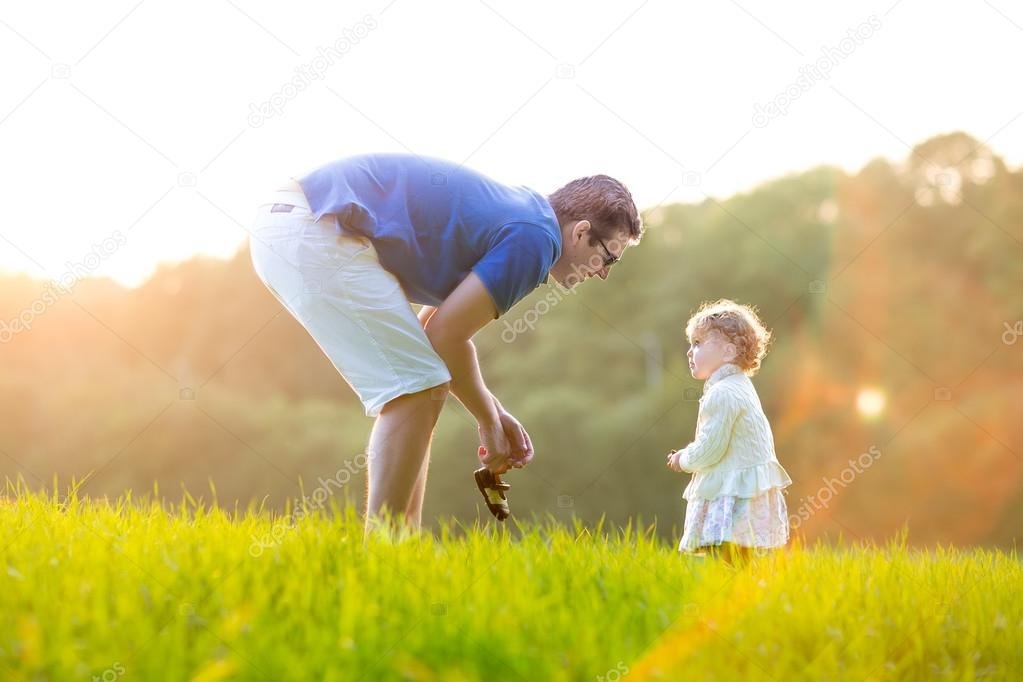 Father playing with his baby daughter in a field
