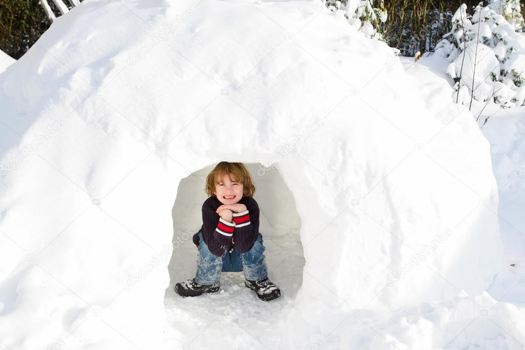 Boy playing in a snow igloo on a sunny winter day