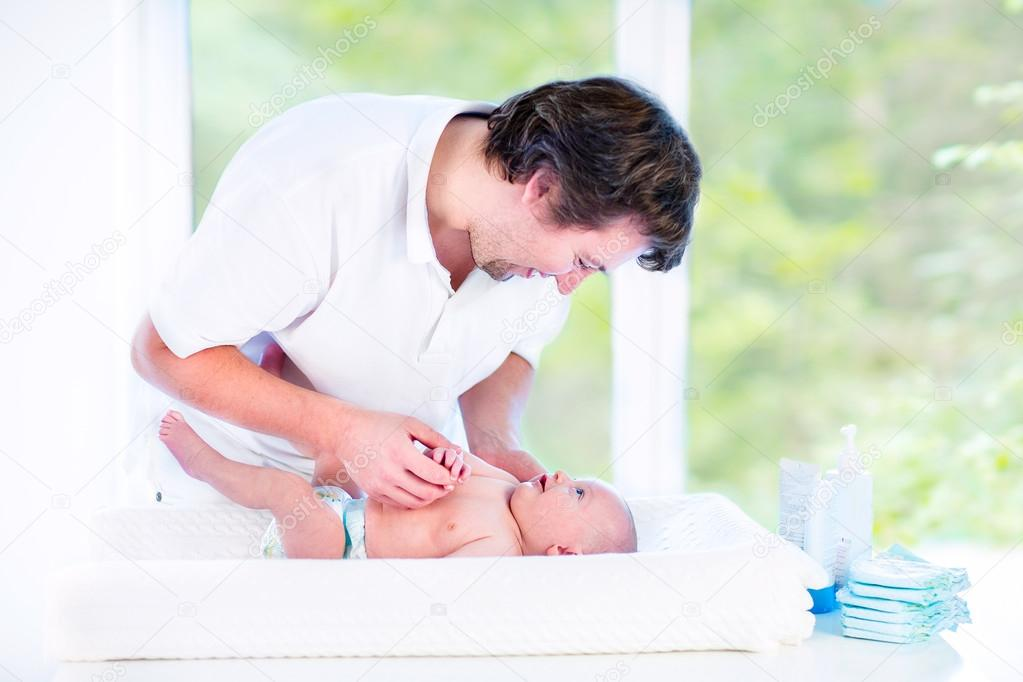 Young loving father changing diaper of his newborn baby son
