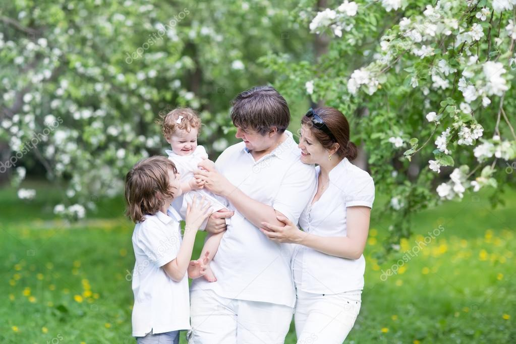 Family in a blooming apple tree garden