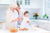 Fényképek sütés süteményt vezető anyjával és aranyos kisgyermek lány nő
