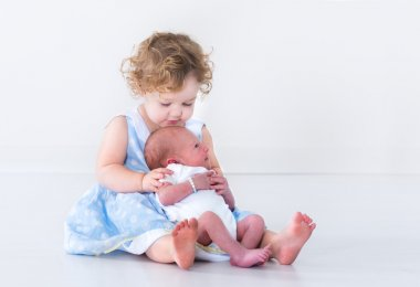 Toddler girl with her newborn baby brother