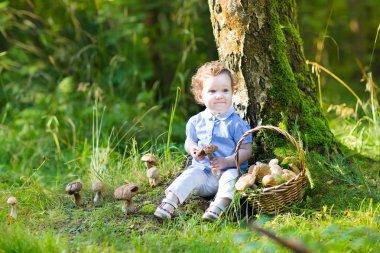 Baby girl gathering mushrooms