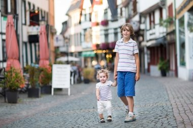 Brother and his little baby sister walking and playing in a shopping street