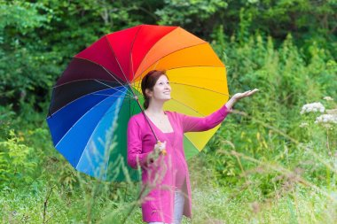 Pregnant woman walking under a colorful umbrella