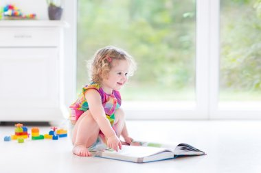 Toddler girl reading a book sitting on a floor