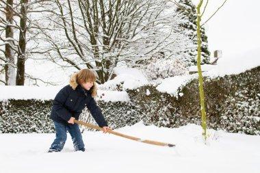 bir bahçe kar kürekle çocuk