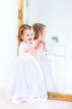 Toddler girl in a white dress