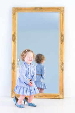 Girl standing in front of a big mirror