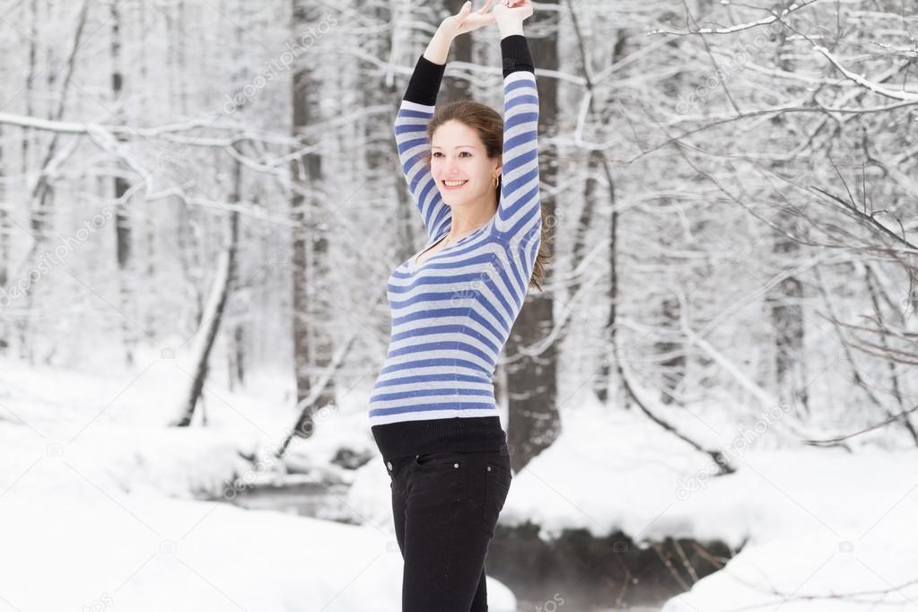 Pregnant woman walking in a snowy park
