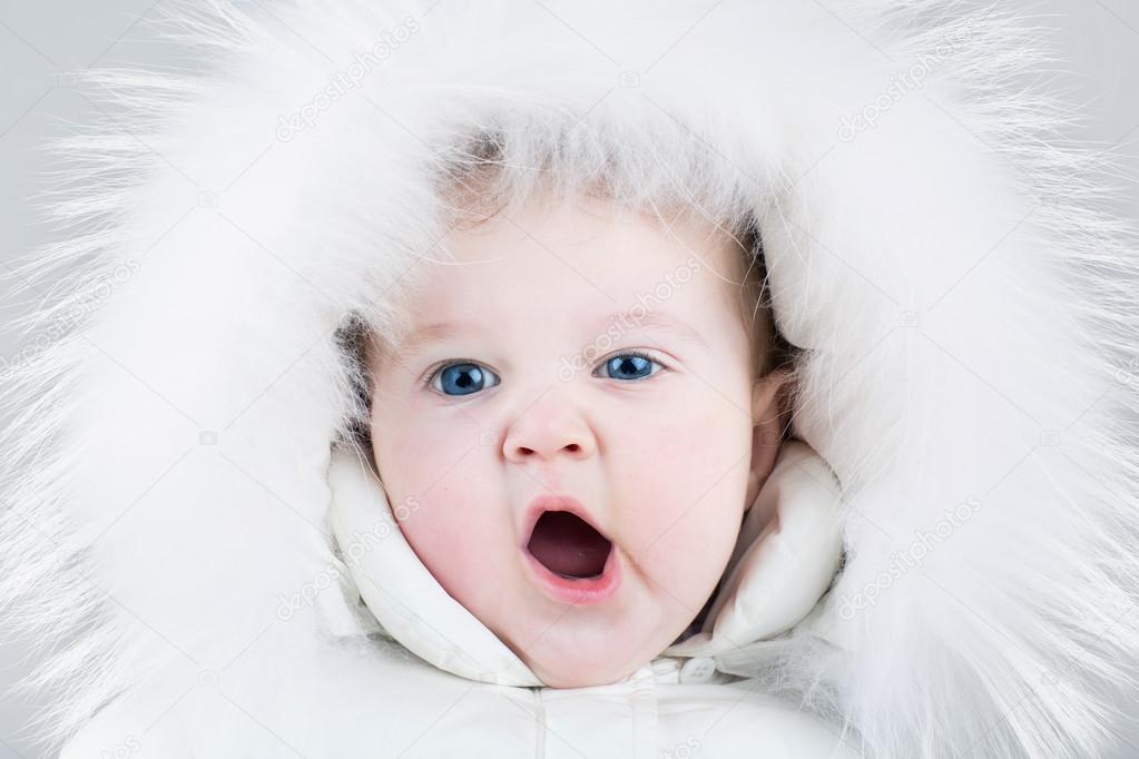 Funny sweet baby girl wearing a big fur hat and a white winter snow suit on light  blue background — Photo by FamVeldman 7f995551edf0