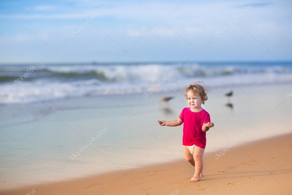 Beautiful baby girl running on a beach
