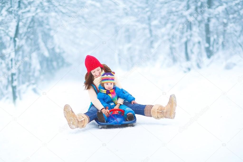 Mother and her little toddler daughter enjoying a sledge ride