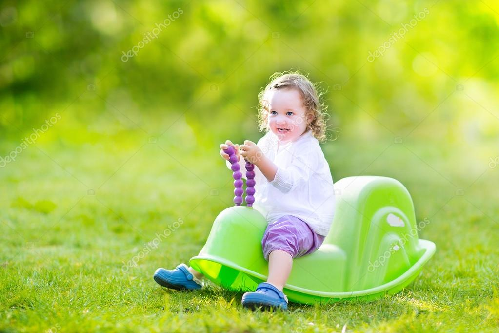 Toddler girl on a swing in a sunny garden