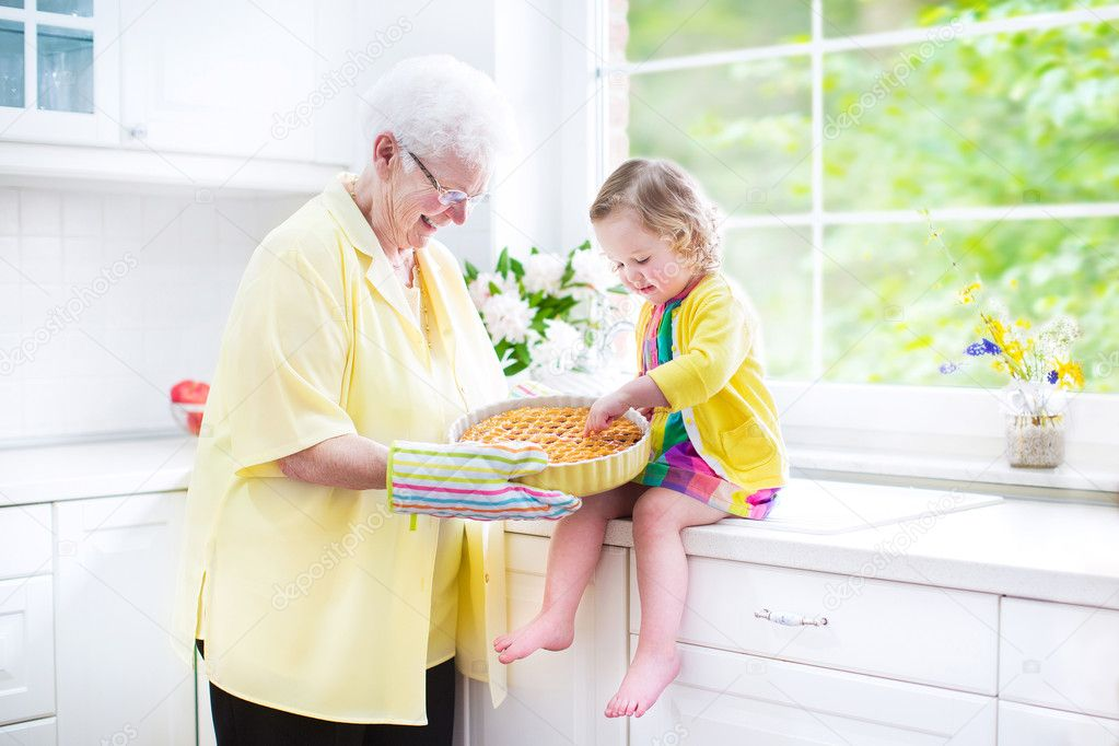 Happy grandmother and little girl baking a pie in a white kitche