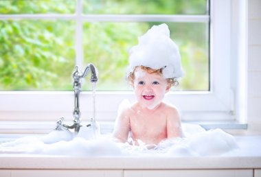 Funny baby girl playing with water and foam in a big kitchen sin