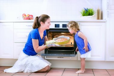 Mother and baby daughter baking a pie