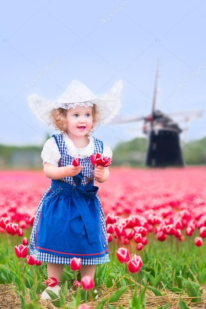 Adorable curly toddler girl wearing Dutch traditional national costume dress and hat playing in a field of blooming tulips next to a windmill