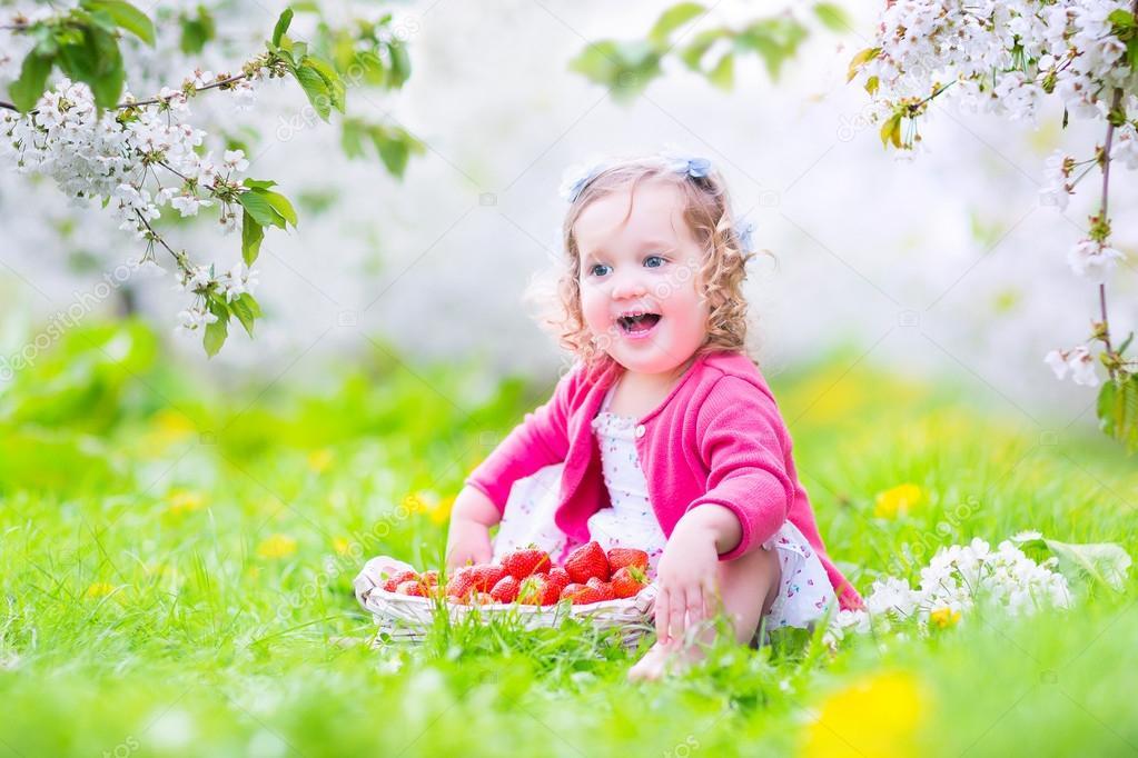 Toddler girl eating strawberry in blooming garden