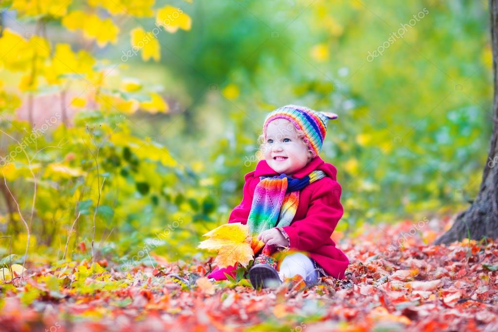 Little girl having fun in an autumn park