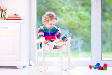 Little girl with a book in a rocking chair