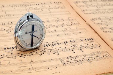 Pocket metronome  on an ancient music score