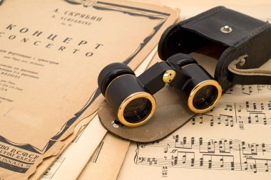 Opera glasses with case on an ancient music score